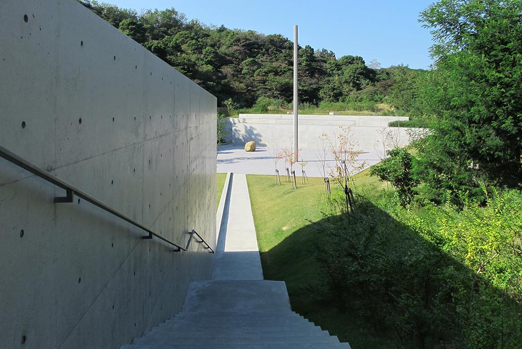 美術館へはコンクリート壁が視界を遮る階段を下りていく