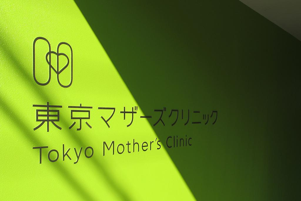 黄緑色の壁にシンプルなロゴ